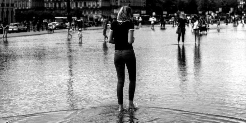 Deszczowo. Bosa dziewczyna na zalanym wodą placu.