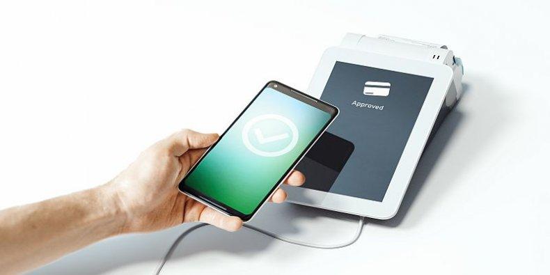 Ręka trzyma telefon komórkowy przy terminal płatniczym POS.