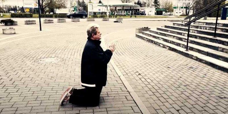 Kazik klęczy przed urzędem na Białołęce - kadr z teledysku